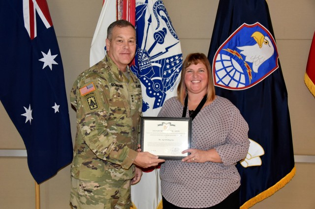 Lt. Gen. James H. Dickinson, commanding general, U.S. Army Space and Missile Defense Command, presents April S. Pellegrino, operations officer, Army Space Personnel Development Office, Space and Missile Defense Center of Excellence, with the command's 2019 Civilians of the Year for supporting staff category award during a ceremony Nov. 15 at the command's Peterson Air Force Base, Colorado, headquarters. (U.S. Army photo by Dottie White)