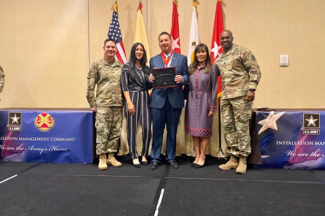 Mike Beando, Director of Human Resources for U.S. Army Garrison Ansbach, received the 2019 IMCOM Stalwart Award during the Senior Leaders and Garrison Commanders Conference Nov. 19, 2019 in San Antonio, Texas. He is pictured with his spouse Arlene, and daughter Mikaela, as well as Col. Steven M. Pierce, USAG Ansbach commander (far left) and Command Sgt. Maj. Philson Tavernier (far right).