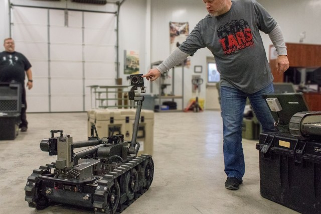 Bill Hagerty, Robotics University new equipment trainer, points to the new thermal vision camera atop the MTRS Inc II robot. The robot will soon replace its predecessor, the Talon 5, and boasts an array of improvements.