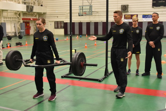 U.S. Army Sgt. Brenda Marquez, left, a member of an Army Combat Fitness Test (ACFT) Mobile Training Team, demonstrates the three-repetition maximum deadlift portion of the new Army Combat Fitness Test, as Sgt. First Class Joseph Brown explains it to observers at Specker Field House at Fort Belvoir, Va., April 10, 2019. The Mobile Training Team demonstrated the ACFT for military and civilian attendees of the Army World Wide Inspector General Conference.