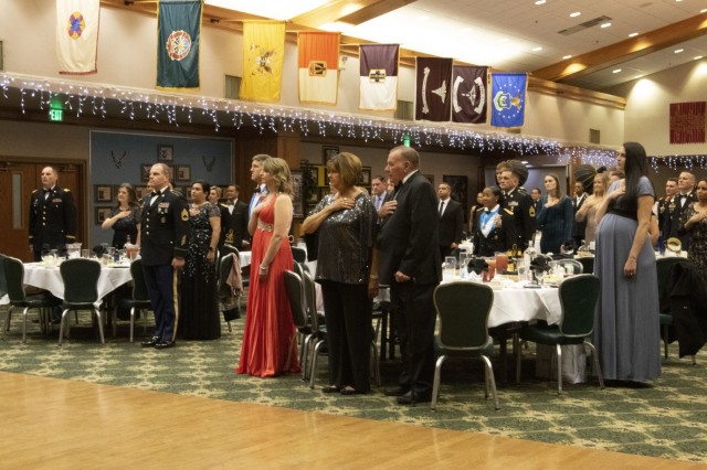 Soldiers and Civilians with ties to the 303rd MI BN stand for the playing of the National Anthem during a ball ceremony, Nov. 22, 2019, Fort Hood, Texas. The special guest during the ball was Ret. Command Sgt. Maj. Daniel Morelock. (U.S. Army photo by Sgt. Melissa N. Lessard)