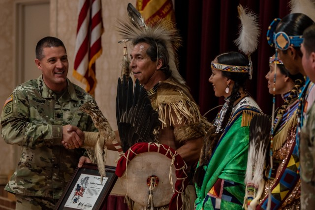 Lt. Col. Vance Brunner, commander of Headquarters Command Battalion at Joint Base Myer-Henderson Hall presents members of the Piscataway Indian Nation Singers and Dancers with a Certificate of Achievement during a celebration for National American Indian Heritage Month at the Community Center on JBM-HH, Virginia, November 13, 2019.