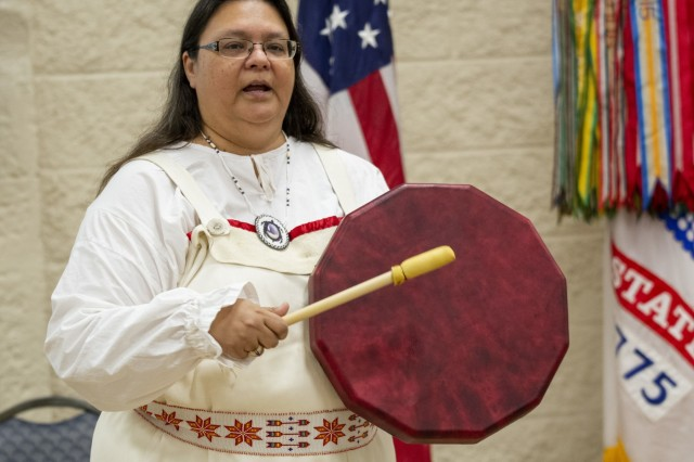 Guest speaker Kim Sigafus McIver sings an Ojibwa lullaby at the National American Indian Heritage Month Observance held at Rock Island Arsenal, Illinois, Nov. 21. She explained how, in her culture, the drum is considered a woman's instrument -¬- it represents Mother Earth and always has a steady beat, like a heart. (Photo by Linda Lambiotte, ASC Public Affairs)