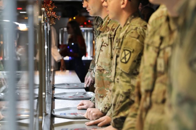 Soldiers of 2nd Brigade Combat Team, 10th Mountain Division move through a line inside the Commando Café as leaders from across the Commando brigade serve lunch during a superhero themed Thanksgiving meal, November 26, 2019, at Fort Drum, New York. Culinary service Soldiers from across the Commando brigade spent weeks preparing for the special holiday meal. (U.S. Army photo by Staff Sgt. Paige Behringer)