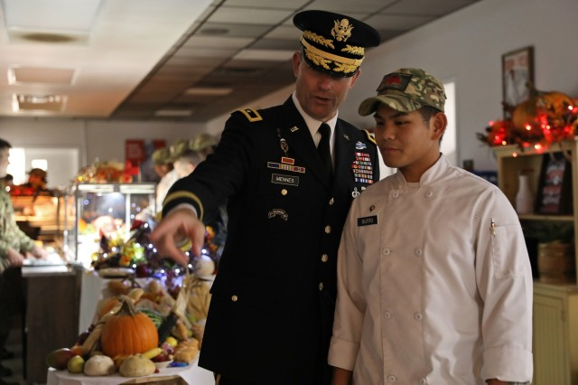 Maj. Gen. Brian Mennes (left), the 10th Mountain Division commander, speaks with Spc. Christian Busto, a culinary service specialist assigned to 4th Battalion, 31st Infantry Regiment, after presenting Busto with a coin to recognize his hard work while preparing for the 2nd Brigade Combat Team, 10th MTN superhero themed Thanksgiving meal, November 26, 2019, at Fort Drum, New York. Culinary service Soldiers from across the Commando brigade spent weeks preparing for the special holiday meal. (U.S. Army photo by Staff Sgt. Paige Behringer)