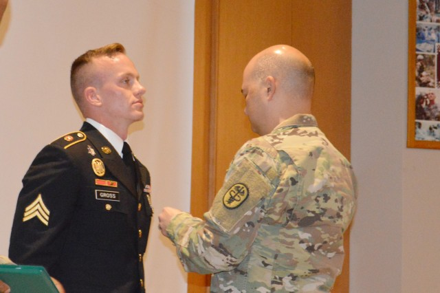 Army Col. Joseph Novak, Brooke Army Medical Center deputy commander for medical services, pins the Army Commendation Medal on Army Sgt. Henry Gross III, Troop Command C Company, for being chosen BAMC's Noncommissioned Officer of the Year during a ceremony Nov. 22, 2019. Gross is a radiology specialist from Fort Pierce, Florida.