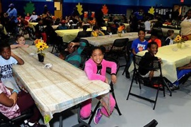 Kids wait for dinner during the Thanksgiving feast at the School Age Center on Thursday.