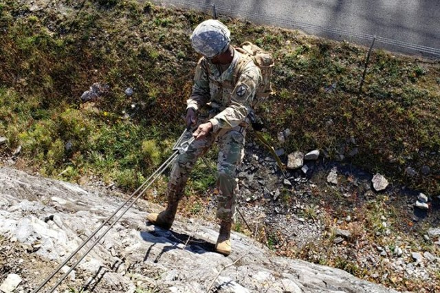 Spc. Adrian Thomas, a (68W) Combat Medic Specialist for the 10th Headquarters and Special Troops Battalion, 10th Mountain Division (LI) Sustainment Brigade repels a cliff during  Mountain Warfare Course held by the Light Fighter's School in Fort Drum, NY.