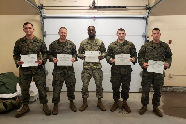 Spc. Adrian Thomas, (middle), receives a certificate for completing the 10th Mountain Division (LI) Mountain Warfare Course as the only junior enlisted U.S. Army Soldier in the course Nov. 6, 2019 at Fort Drum, NY.
