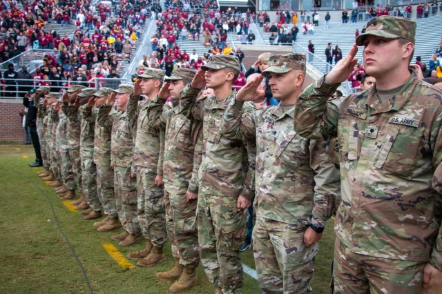 Soldiers from 703rd Brigade Support Battalion, 2nd Armored Brigade Combat Team, 3rd Infantry Division, salute the American flag during a military appreciation football game Nov. 16, at Doak Campbell Stadium. Each year FSU hosts an annual football game to highlight the selfless service of Soldiers, retirees, and family members that served in the military. (U.S. Army photo by Spc. Devron Bost/released)
