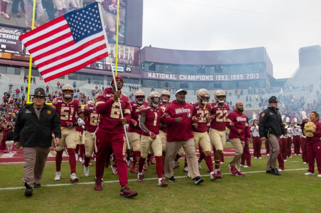 A player from the Florida State University football team carries the American flag onto the field before the Seminoles annual military appreciation game Nov. 16, at Doak Campbell Stadium. Military service members were involved in a variety of activities to celebrate Veterans Day before and during the game, FSU defeated the University of Alabama State 49-12. (U.S. Army photo by Spc. Devron Bost/released)