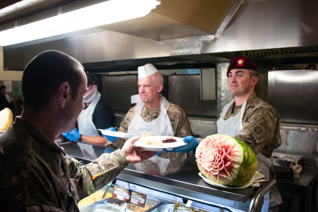 Maj. Jesse Kadle, right, assigned to the 3rd Brigade Combat Team, 82nd Airborne Division and Lt. Col. John Cole, assigned to the 3rd Infantry Division, center, serve Thanksgiving meals at Kandahar Airfield, Afghanistan on Thursday, November 28, 2019 while deployed in support of Operation Freedom's Sentinel.