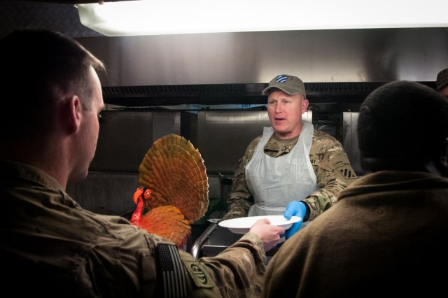Col. Trevor Bredenkamp, center, assigned to the 3rd Infantry Division and Commander of Train, Advise, Assist, Command-South serves Thanksgiving meals at Kandahar Airfield, Afghanistan on Thursday, November 28, 2019 while deployed in support of Operation Freedom's Sentinel.