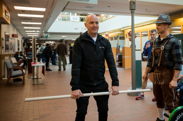 Physical therapist 1st Lt. Tyler Simmet advises Col. Scottie Roofe, the deputy commanding officer, on proper form before he steps over to try his hand at the deadlift in the Medical Mall at Madigan Army Medical Center's inaugural Volksmarch on Joint Base Lewis-McChord, Wash., on Nov. 23.