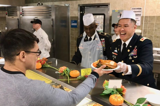 Col. Fred Dela Cruz , chief of staff, 19th Expeditionary Sustainment Command shares a laugh with a guest at the Thanksgiving Dinner celebration at the Sustainer Grill Dining Facility on Camp Henry, Nov. 28. Following military tradition, leadership from throughout 19th ESC joined Eighth Army and USAG Daegu leaders to serve dinner to Soldiers, civilians, Republic of Korea partners and families.