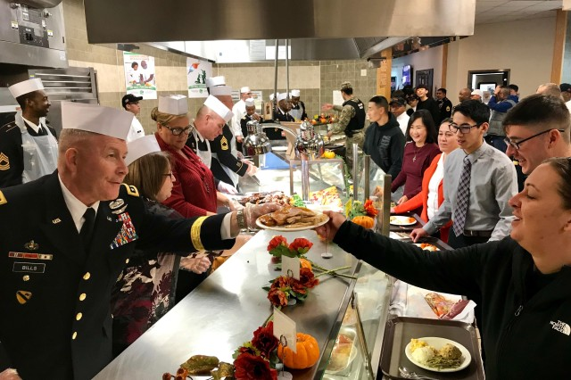 Lt. Gen. Michael A. Bills, commanding general, Eighth Army, hands a plate to a guest during the Thanksgiving Dinner celebration at the Sustainer Grill Dining Facility on Camp Henry, Nov. 28.  Bills, along with Command Sgt. Major Jason Schmidt, senior enlisted Soldier, Eighth Army, and their spouses, traveled from Camp Humphreys to join 19th ESC and USAG Daegu leaders to serve dinner to Soldiers, civilians, Republic of Korea partners and families.