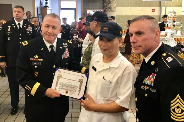 Lt. Gen. Michael A. Bills, commanding general, Eighth Army and Command Sgt. Major Jason Schmidt, senior enlisted Soldier, Eighth Army, recognize Pak Yong with a Certificate of Appreciation during the Thanksgiving Dinner celebration at the Sustainer Grill Dining Facility on Camp Henry, Nov. 28.  Pak, along with members of the 541st Field Feeding Company, 498th Combat Sustainment Support Battalion, were responsible for the Thanksgiving meal which fed more than 500 Soldiers, civilians, Republic of Korea partners and families in Area IV.