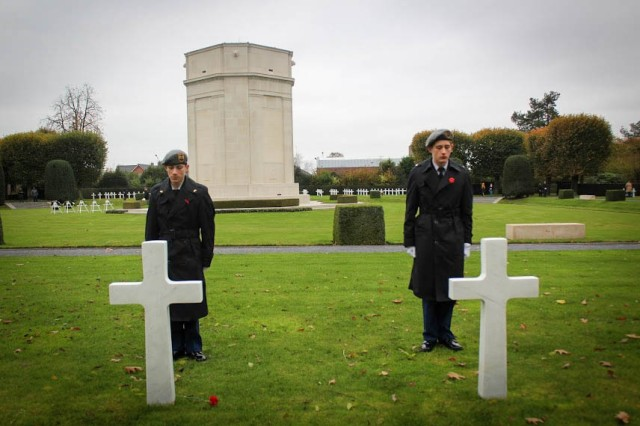 Left, Private 1st Class Collin Robertson and Maj. Cooper Robertson (brothers), 9th Battalion Junior Reserve Officer Training Corps cadets, pay honors to fallen WWI Soldiers at Flanders American Cemetery during a visit to Ypres, Belgium Nov. 8-11 to study WWI.