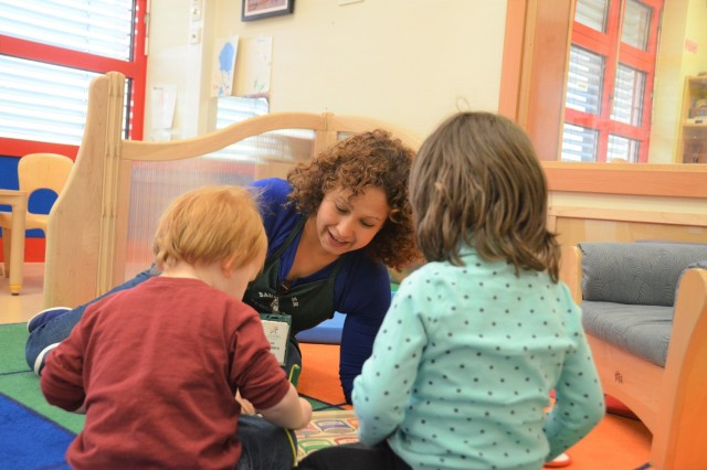 A Smith Child Development Center caregiver interacts with children in a play group in Baumholder, Germany. Smith CDC is one of seven Army CDCs offering child care in the U.S. Army Garrison Rheinland-Pfalz footprint.