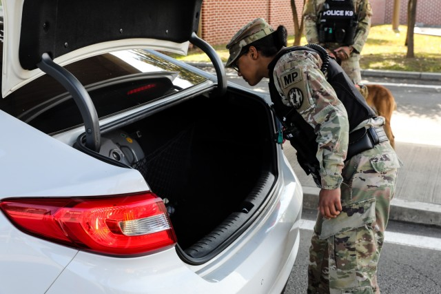 Pvt. 1st Class Tanita Hartl, an MP with 401st Military Police Co.is searching the trunk of a vehicle that is coming base at Camp Casey, Republic of Korea, Oct. 17, 2019. The 401st MP Co. is currently attached to 3rd Armored Brigade Combat Team, 1st Cav. Div. during its rotation to the Republic of Korea. (Photo by Staff Sgt. Jacob Kohrs)