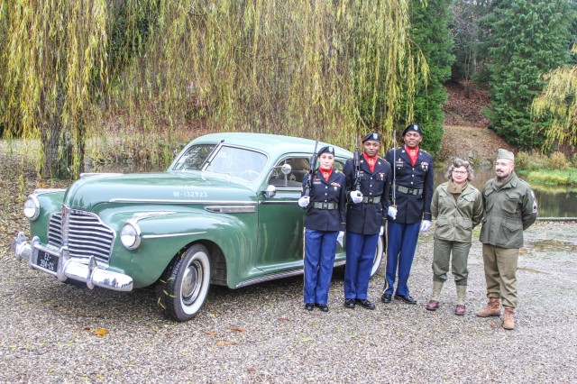Thannenkirch, FRANCE - (left to right) Sgt. Emily Priselac, Pvt. 2 Shaunequez Martin and Staff Sgt. Kevin Outlaw, assigned to the 5th Battalion, 7th Air Defense Artillery Regiment stand with Marc and Maryline Eberhardt, World War II reenactors and enthusiasts, in front of a Dec. 1941 Buick Super 8 series car, designed to resemble an officer's staff car at the 75th Anniversary of the liberation of thannenkirch, France, Dec. 1. The commemoration included a wreath laying ceremony at the town church, an unveiling of a commemorative plaque honoring the men of the 4th Battalion of the 142nd Infantry Regiment of the 36th Division of the 7th US Army who liberated Thannenkirch and the inauguration of a commemorative plaque on the birthplace of Armand Schiber, a French resistance member and deported soldier who died in Buchenwald.