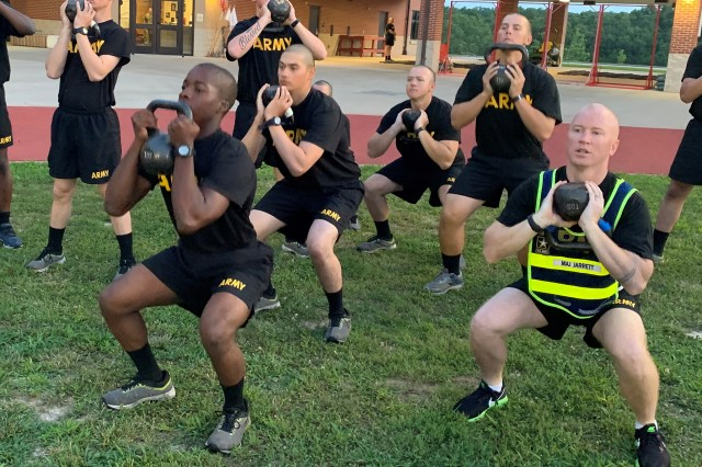 Maj. Edward Jarrett, U.S. Army Engineer School executive officer, right, performs goblet squats with trainees assigned to Company D, 31st Engineer Battalion. The company is piloting a new concept in physical readiness called the Strength Training Program, which is designed to reduce injuries throughout Basic Combat Training.