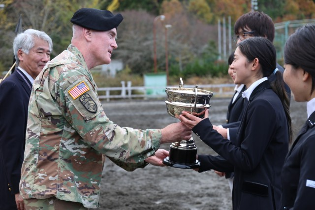 Col. Marvin Emerson, commander of U.S. Army Medical Activity -- Japan, hands the BG Sams Equestrian Cup to Moe Kanda, the winner of the 71st annual BG Sams Equestrian Cup, held Nov. 24 at Tsukui Equestrian Park.