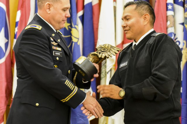 Lt. Col. Sean P. McBride, 602nd Aviation Support Battalion, 2nd Combat Aviation Brigade battalion commander, presents Cpt. Sean A. Begaye, with a Native American chief bust statue, as a token of appreciation for his service and dedication, Nov. 27.