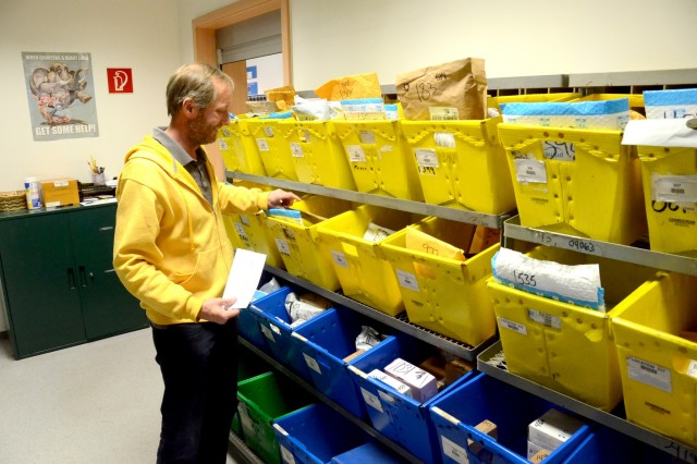 David Chinchen, USAG Rheinland-Pfalz Rhine Ordnance Barracks postal service employee, checks the small packages boxes for a customer's mail at the ROB Postal Services Center package pickup window.