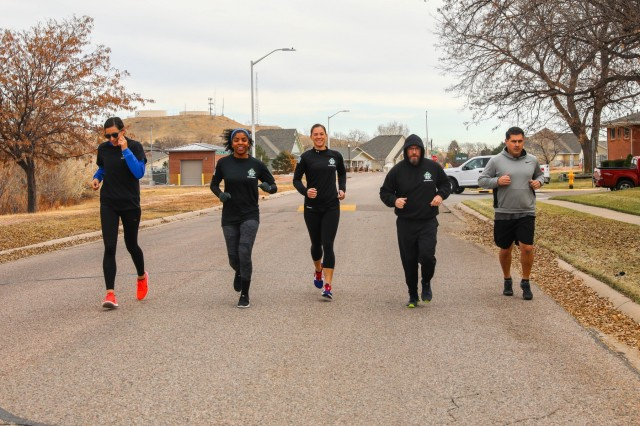 Family members and friends from the 704th Brigade Support Battalion, 2nd Infantry Brigade Combat Team, 4th Infantry Division, run as a group on a street on Fort Carson, Colorado, Nov. 15, 2019, as part of the battalion's 'Spouses Physical Training.' Joe Sullivan, family readiness group leader for the battalion and spouse of 704th BSB commander, hosts the program every Friday for all spouses in the battalion. (U.S. Army photo by Staff Sgt. Neysa Canfield)