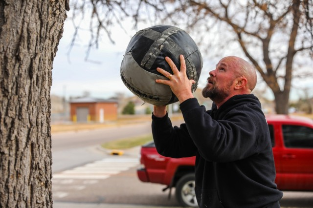 """Joe Sullivan, Family Readiness Group leader for 704th Brigade Support Battalion, 2nd Infantry Brigade Combat Team, 4th Infantry Division, prepares to throw a medicine ball Nov. 15, 2019, during """"Spouses Physical Training"""" at Fort Carson, Colorado. (Photo by Staff Sgt. Neysa Canfield)"""
