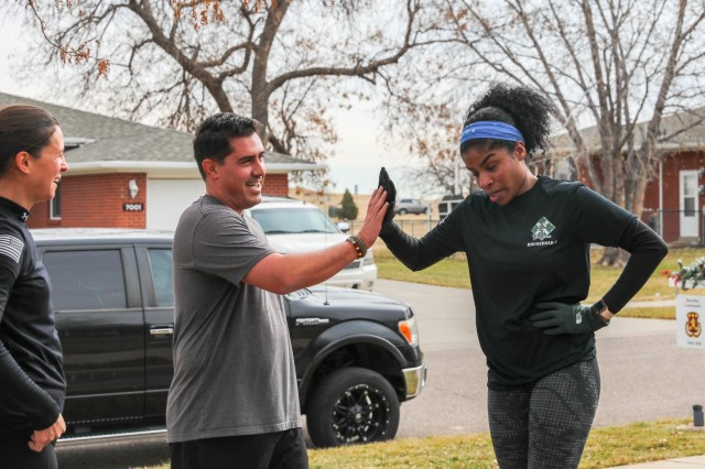 """Members of the """"Spouses Physical Training"""" program from the 704th Brigade Support Battalion, 2nd Infantry Brigade Combat Team, 4th Infantry Division, high-five each other after a tough workout Nov. 15, 2019. Family members and friends of the battalion participate in the physical fitness program every Friday. (Photo by Staff Sgt. Neysa Canfield)"""