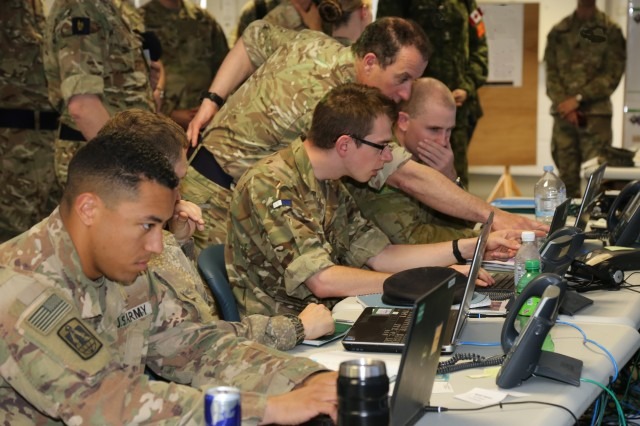 U.S. and coalition Soldiers monitor the tactical network and the common operational picture at the Coalition Network Operations and Security Center during the Joint Warfighting Assessment 18.1 at Grafenwohr, Germany, on May 3, 2018. The Global Agile Integrated Transport (GAIT) network design enables units in theater and/or at home station to share mission command, network operations and the coalition common operating picture.
