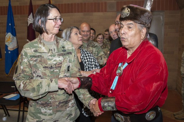 Erwin De Luna and Brooke Army Medical Center Commanding General Brig. Gen. Wendy Harter lead BAMC staff members in a traditional Native American dance during the National American Indian Heritage Month observance Nov. 26, 2019. De Luna is president of the board of directors for the United San Antonio Pow Wow Inc., and is of Taos Pueblo and Navajo ancestry.