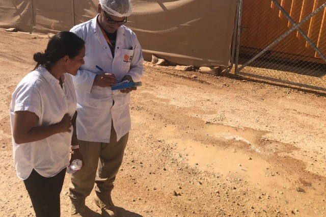 Sgt. 1st Class Jenny Cisneros, left, checks records with a civilian contractor at the Al Zarqa Joint Training Center in Jordan. Cisneros is an administrative contracting officer at the Al Zarqa Joint Training Center in Jordan.