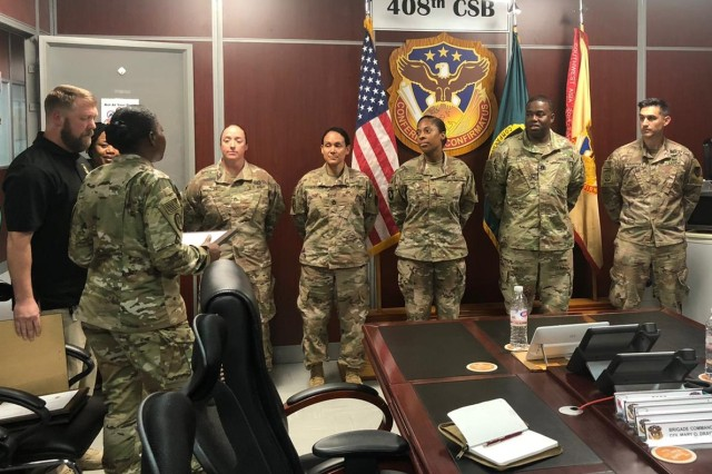 Col. Mary Drayton presents framed warrants to, from left, Staff Sgt. Stephanie Nye, Sgt. 1st Class Jenny Cisneros, Staff Sgt. Kassandra Robinson, Capt. Corey Griffin and Maj. Michael Krivensky during a recent ceremony in Kuwait. Drayton is the 408th Contracting Support Brigade commander. Nye, Cisneros, Robinson, Griffin and Krivensky are administrative contracting officers in various locations in Jordan and Iraq and members of the 605th Contracting Team.