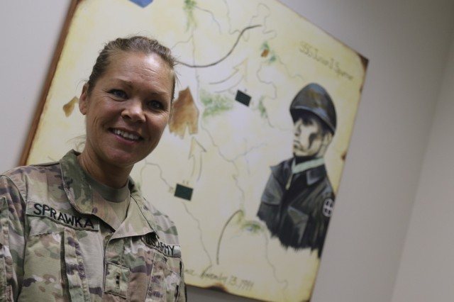 """CAMP ARIFJAN, Kuwait - Chief Warrant Officer 2 Carol Sprawka, 35th Infantry Division, poses with the portrait she painted of World War II Medal of Honor Recipient Staff Sgt. James Ira """"Junior"""" Spurrier Dec. 22, 2017. The painting now hangs at the 35th Inf. Div.'s forward deployed headquarters in the newly-dedicated Spurrier Conference Room, renovated and named for the division's historic figure. (U.S. Army photo by Master Sgt. Mark Hanson)"""