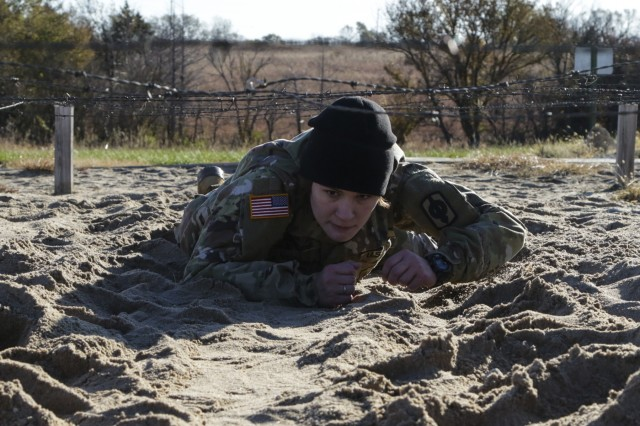 Sgt. Brena Child, a human resource sergeant assigned to Headquarters and Headquarters Battery, 997th Brigade Support Battalion, 130th Field Artillery Brigade, performs the belly crawl on one of the obstacles on an Air Assault obstacle course at Fort Riley, Kansas, during the 2019 annual KSARNG Best Warrior Competition Nov. 2, 2019. Competitors completed an Army Physical Fitness Test, day and night land navigation, weapons qualification, an Air Assault obstacle course, a call for fire exercise and a ruck march. Additionally, they tested on the new Army Combat Fitness Test.