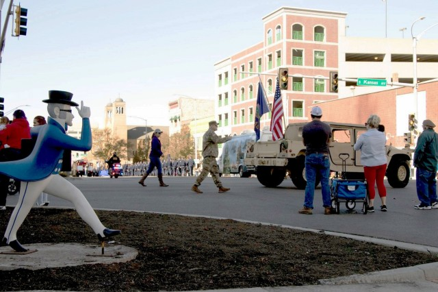 Master Sgt. Clint Barnett, the operations noncommissioned officer for 269th Troop Command, gives parade-goers a thumbs up while walking behind a Kansas Army National Guard Humvee in the Topeka Veterans Day Parade, Nov. 9, 2019.