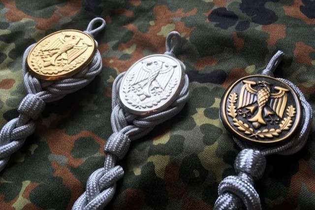 The German Schützenschnur badges - gold, silver and bronze. This is a highly sought-after award that includes several requirements during the event.  Participants must successfully shoot from all three classes of weapons: Pistol, rifle and heavy weapon.