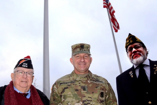 George Gilgore, left, Veterans of Foreign Wars Post GR-1, Command Sgt. Maj. Brett Waterhouse, USAG Rheinland-Pfalz command sergeant major and David Garcia, right, VFW Post GR-1 commander, pose in front of the newly installed flags on Rhine Ordnance Barracks.