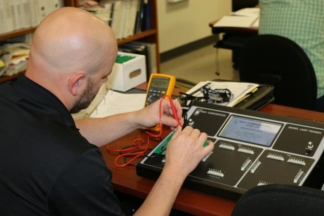 Stephen Atteberry, an apprentice trainee, measures the resistance of different circuits prior to energizing a test board.