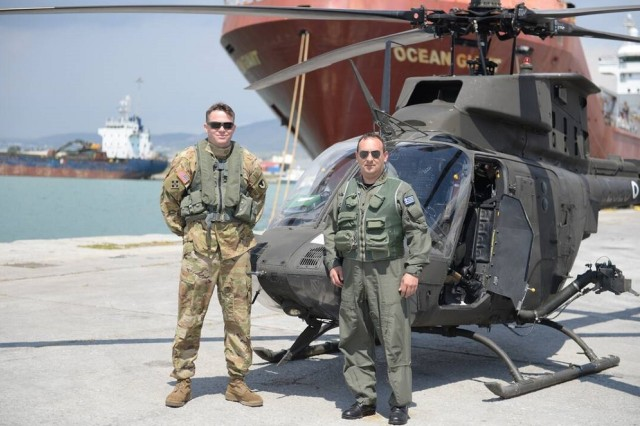 Chief Warrant Officer 3 John Meadows, left, stands with the battalion commander of the Greek Army helicopter training unit at the Greek port of Volos, before flying the newly arrived helicopters to the Hellenic Army Aviation air base at Stefanovikio, Greece.