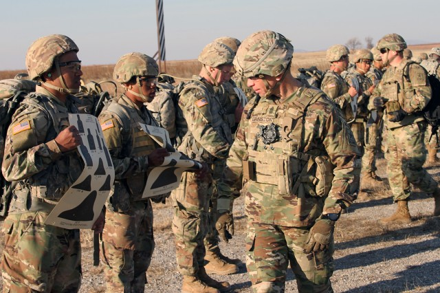 Sgt. Maj. of the Army Michael A. Grinston (center) looks over the paper targets that  basic combat trainees shot Dec. 6, 2019, the 25 Meter II Range at Fort Sill, Oklahoma. The trainees were from B Battery, 1st Battalion, 19th Field Artillery.