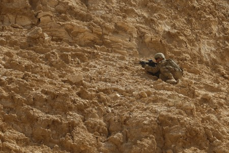 A Soldier from the Mississippi National Guard readies his position for cover fire as a part of team movement drills through a wadi in Rabkoot, Oman, Jan. 28, 2019. 'Wadi' translates to 'valley' from Arabic to English. The U.S. Army and the Royal Army of Oman conducted team, squad, and platoon maneuvers during exercise Inferno Creek 19. The bilateral exercise was an opportunity for both militaries to build tactical proficiency and gain shared understanding of each other's forces and support long-term regional stability. (U.S. Army National Guard photo by Sgt. Linsey Williams)