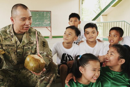 U.S. Army Sgt. Kyle Horiuchi visits with local children during a catered lunch at the Engineering Civic Action Project 4 opening ceremony as part of Exercise Balikatan, March 12, 2019. Exercise Balikatan is an annual U.S.-Philippine military training exercise focused on a variety of missions, including humanitarian assistance and disaster relief, counterterrorism, and other combined military operations. (U.S. Army photo by Sgt. Scott Vargas)