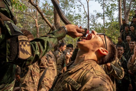 Royal Thai Armed Forces Master Sgt. 1st Class Saengchai Seeuthai pours cobra blood into the mouth of a U.S. Soldier of the 20th Infantry Regiment during exercise Cobra Gold 19 in Phitsanulok, Thailand, Feb. 13, 2019. (U.S. Marine Corps photo by Cpl. Robert Gavaldon)