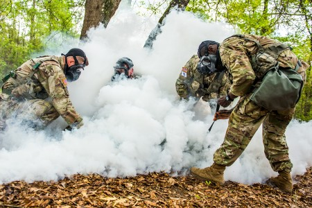 A team dons gas masks during the trauma lane for the Best Mortar Competition, Fort Benning, Ga, April 10, 2019. After three days of competition among 19 U.S. Army mortar teams and one Dutch army mortar team, the 82nd Airborne Division prevailed as champions during the competition. (U.S. Army photo by Patrick Albright)