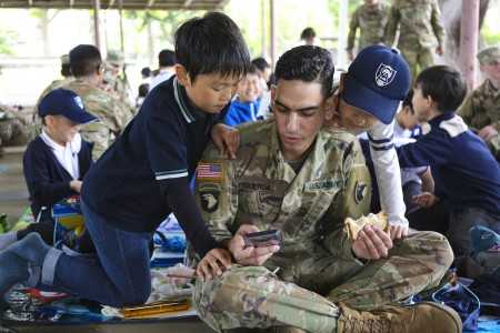 Sgt. Alexander Figueroa, assigned to the 38th Air Defense Artillery Brigade, shows LCA Kokusai Elementary School students a game on his cellphone while eating lunch during an Earth Day event April 24, 2019, at Sagami General Depot, Japan. (U.S. Army photo by Noriko Kudo)