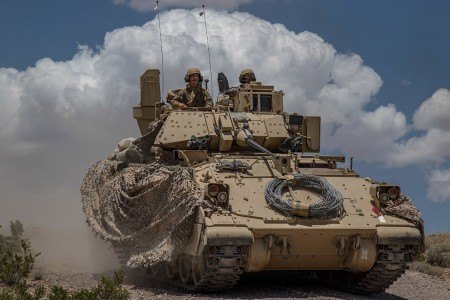 Soldiers from the Montana Army National Guard push on in their Bradley Fighting Vehicle during a defensive attack training exercise at the National Training Center in Fort Irwin, Calif., June 1, 2019. A month-long NTC Rotation provides more than 4,000 service members from 31 states, including units from 13 National Guard states and territories, with realistic training to enhance their combat, support and sustainment capabilities. (U.S. Marine Corps photo by Cpl. Alisha Grezlik)